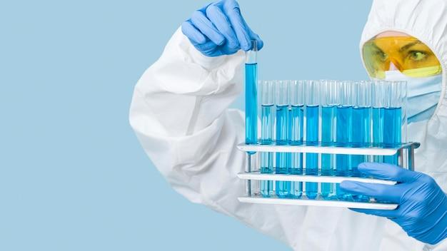 Wetenschapper die blauwe chemicaliën bekijkt