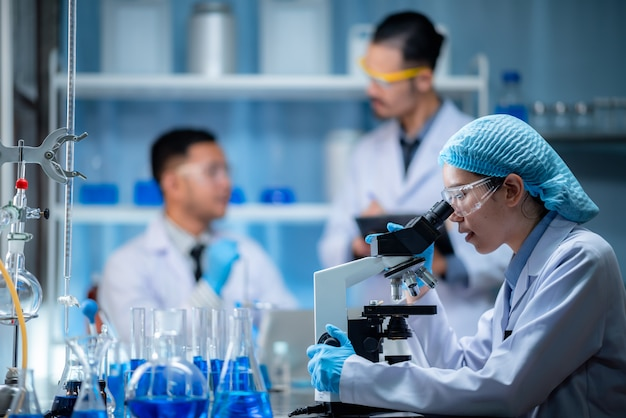Wetenschapper die door een microscoop in een laboratorium kijkt