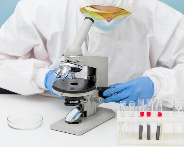 Wetenschapper die door een microscoop kijkt