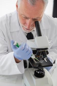 Wetenschapper die door microscoop kijkt
