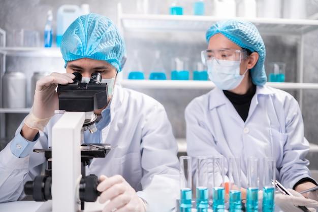 Wetenschapper die door wetenschappelijke microscooplens in laboratorium kijkt, wetenschapper die onderzoek doet op het gebied van geneeskunde, biotechnologie, biologie of chemie, arts die werk analyseert in het laboratorium voor medische microbiologie