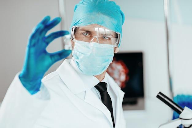 Wetenschapper die een capsule met een nieuwe vaccinwetenschap en gezondheid bekijkt