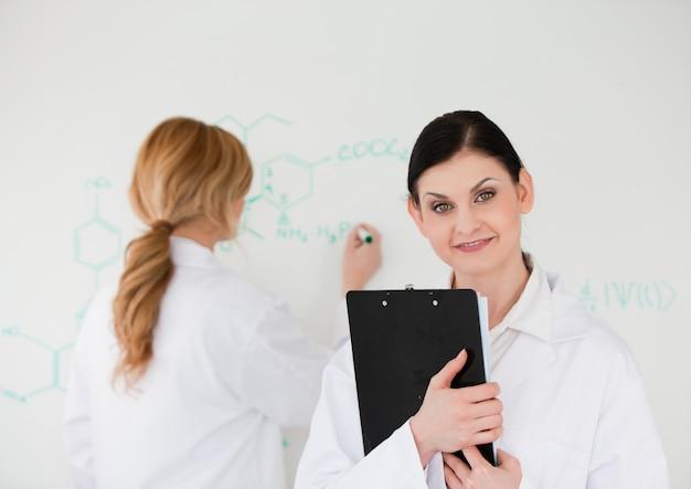 Wetenschapper die een formule schrijft die door haar medewerker wordt geholpen