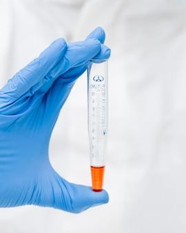 Wetenschapper die een oranje chemisch product houdt