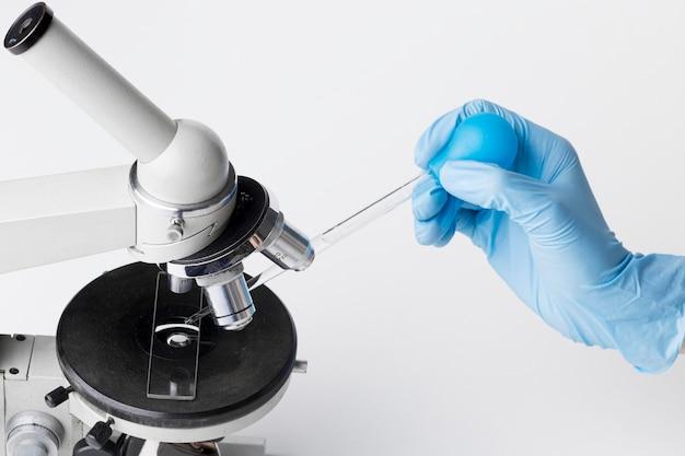 Wetenschapper die een stof in een microscoop aanbrengt