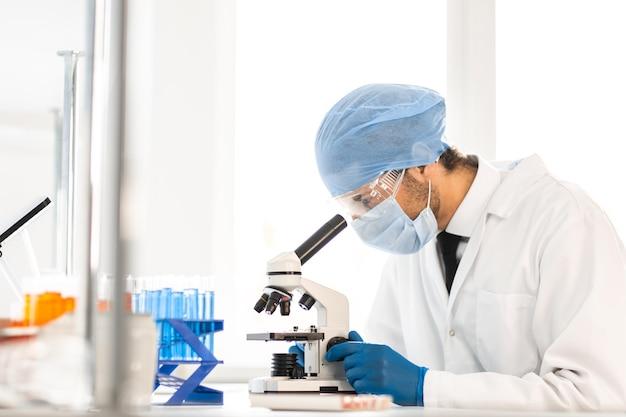 Wetenschapper die het oculair van een microscoop onderzoekt