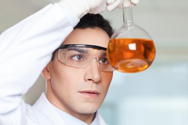 Wetenschapper die in het laboratorium staat en een beker vasthoudt