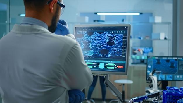 Wetenschapper die in laboratorium werkt en testproefvaccin analyseert en medicijngegevens controleert die voor de pc staan