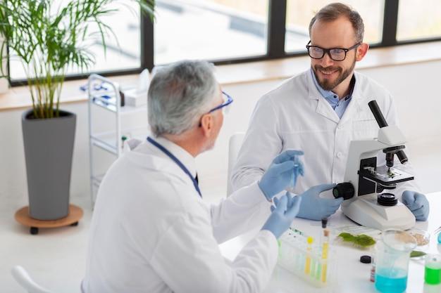 Wetenschapper die met microscoop middelgroot schot werkt
