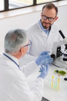Wetenschapper die met microscoop werkt