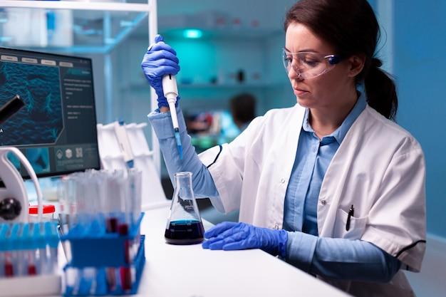 Wetenschapper die micropipet gebruikt om een monster te nemen om het te analyseren in het laboratorium voor medische gezondheidszorg