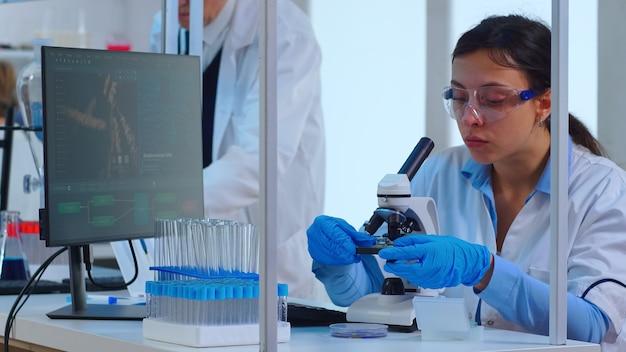 Wetenschapper die onderzoek doet met behulp van een microscoop terwijl collega's aan de achtergrond werken in een modern uitgerust laboratorium. multi-etnische dingen die de evolutie van vaccins analyseren met behulp van hightech voor onderzoek naar behandeling