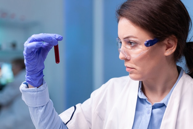 Wetenschapper-dokter in witte jas die genetische infectie ontdekt en een bloedbuis analyseert