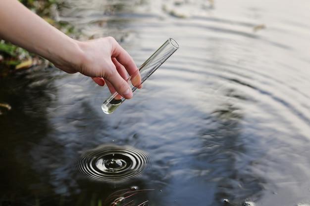 Wetenschapper en bioloog hydrobioloog neemt buiten watermonsters voor analyse.