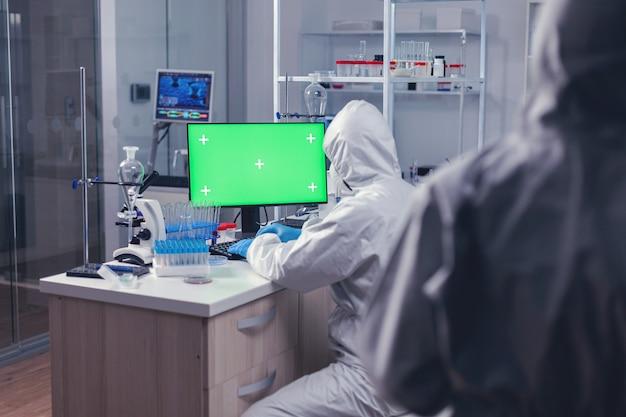 Wetenschapper gekleed in ppe-pak werken op computer met groen scherm tijdens wereldwijde pandemie. team van microbiologen die vaccinonderzoek doen en schrijven op apparaat met chroma key, geïsoleerd, mockup-display.