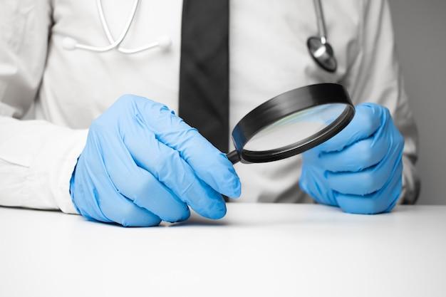 Wetenschapper hand in blauwe handschoen met vergrootglas geïsoleerd op een witte achtergrond