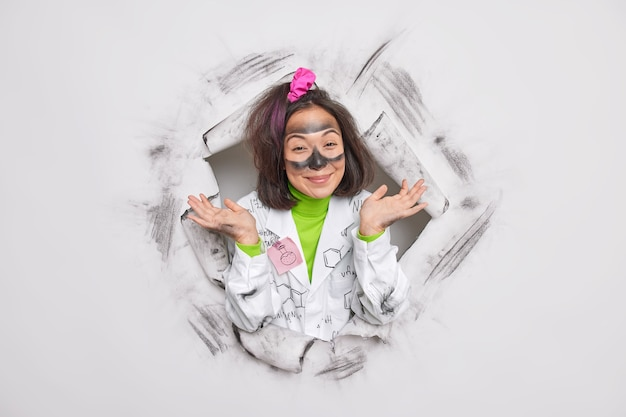 Wetenschapper heeft een onwetende uitdrukking bevredigd, gekleed in een medische jas met formules heeft een vies gezicht na explosie houdt handpalmen opzij poses in papieren gat van wit gescheurd