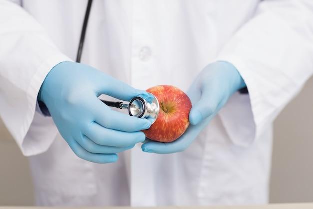 Wetenschapper het luisteren appel met stethoscoop