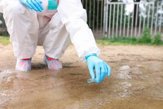Wetenschapper in beschermend pak die water verzamelt in reageerbuis van meerclose-up die kwaliteit controleert