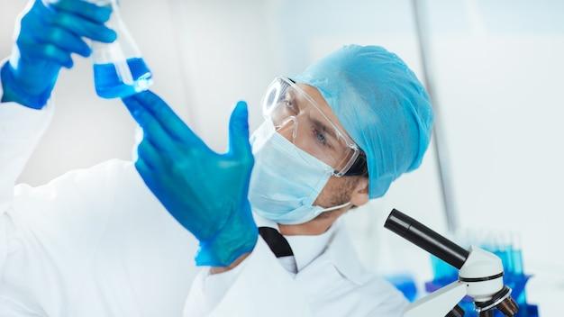 Wetenschapper in beschermende kleding die de vloeistof in de kolf bekijkt.