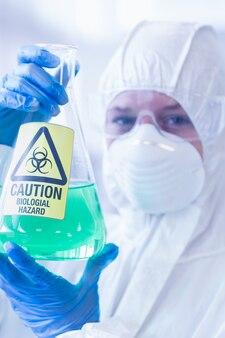 Wetenschapper in beschermende pak met gevaarlijke chemische stof in de kolf