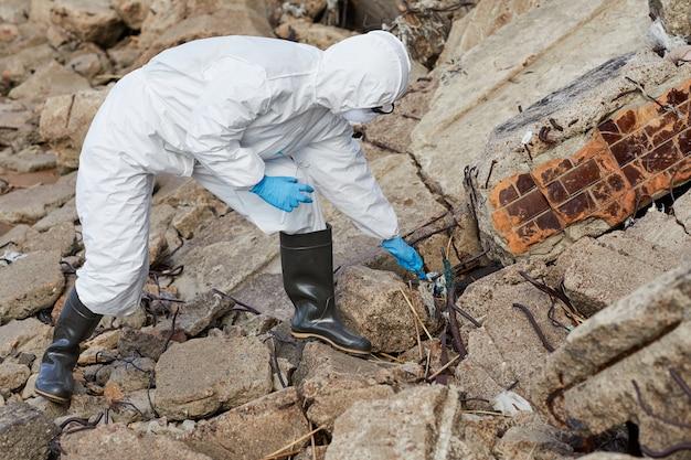 Wetenschapper in beschermende werkkleding staande op de rotsen en het nemen van monsters in de kolf buitenshuis