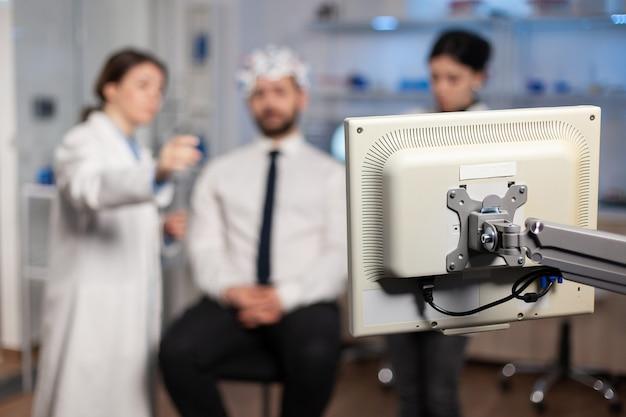 Wetenschapper in hersenstudie bespreekt met patiënt aangesloten wot-elektrodensensoren, evolutie van het zenuwstelsel. medisch team in kliniek met behulp van scanner, tomografie.