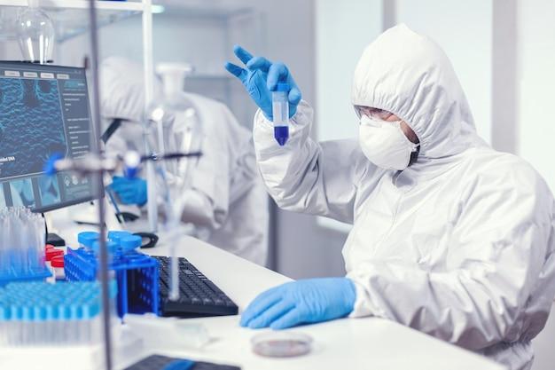 Wetenschapper in laboratoriumhoes kijkt goed naar het monster in de reageerbuis in de loop van het coroanvirus