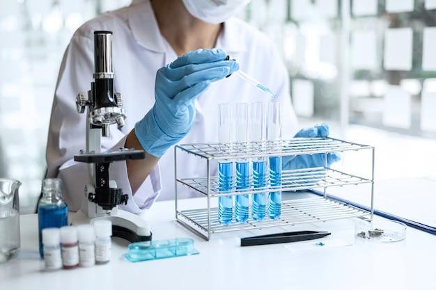 Wetenschapper in laboratoriumjas reageerbuis met behulp van microscoop reagens met druppel kleur vloeistof te houden
