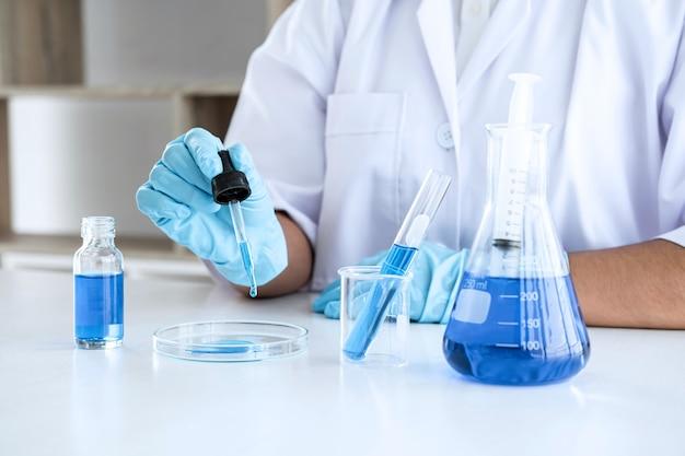 Wetenschapper in laboratoriumjas reageerbuis met reagens met druppel kleur vloeistof over apparatuur te houden