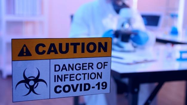 Wetenschapper in pbm-pak doet in een laboratorium onderzoek naar het covid 19-vaccin.