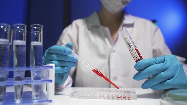 Wetenschapper in ppe-suite doet wat onderzoek en controleert een vloeistof in een reageerbuis in het laboratorium.