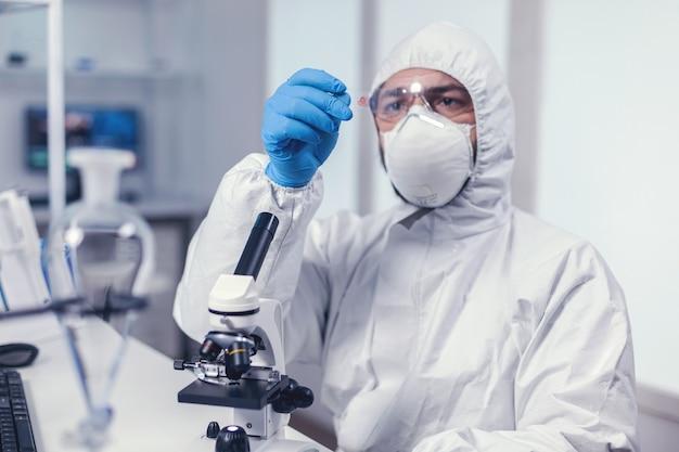 Wetenschapper kijkt naar een microscoopglaasje gekleed in overall tijdens coronavirus