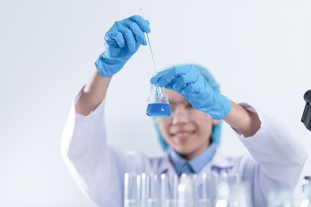 Wetenschapper met apparatuur en wetenschappelijke experimenten, laboratoriumglaswerk dat chemische vloeistof bevat voor onderzoek of het analyseren van een monster in een reageerbuis in het laboratorium.