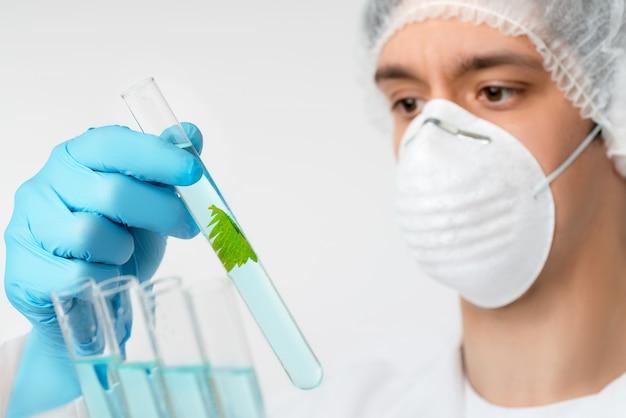 Wetenschapper met bruine ogen in beschermende slijtage met plantenmonster