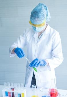 Wetenschapper met een reageerbuis die bij het laboratorium werkt