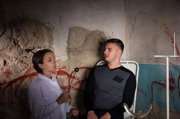 Wetenschapper met ijzeren medisch hulpmiddel voor patiënt in kerker met bloedige muren in een halloween-horrorconcept