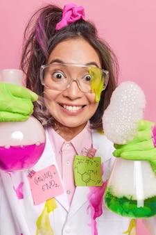 Wetenschapper met laboratoriumglaswerk mengt kleurrijke vloeistoffen of ingrediënten krijgt chemische reactie voert onderzoek uit in laboratorium draagt jas beschermende bril. positieve gezondheidszorgonderzoeker in kliniek