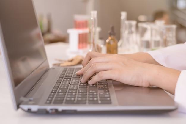 Wetenschapper of artsenhand die op laptop notitieboekjetoetsenbord typen voor testresultaat.
