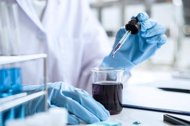 Wetenschapper of medisch in laboratoriumjas met druppelaar met reagens, reagentia in glazen kolf te mengen