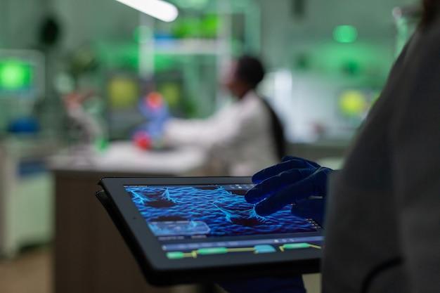 Wetenschapper-onderzoeker arts die genetische mutatietest analyseert met behulp van tablet terwijl haar collega biologische expertise typt op de computer op de achtergrond