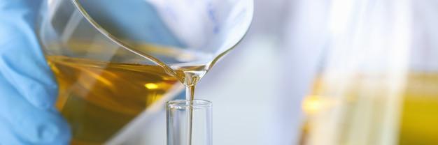 Wetenschapper scheikundige olie uit de kolf gieten in glas close-up kwaliteitscontrole van eetbare oliën