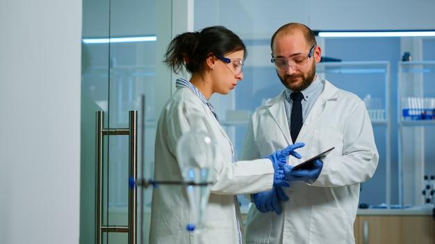 Wetenschapper teamvergadering en bespreking van behandelingsresultaten staan in onderzoekslaboratorium wijzend op tablet. dingen die de ontwikkeling van vaccins tegen het covid19-virus onderzoeken met behulp van hightech voor onderzoek.