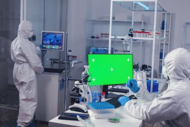 Wetenschapper typen op toetsenbord werkt met computer met groen scherm gekleed in ppe. team van microbiologen die vaccinonderzoek doen en schrijven op apparaat met chroma key, geïsoleerd, mockup-display.