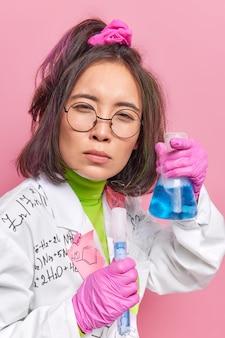 Wetenschapper voert chemisch experiment uit houdt glazen kolven met vloeistof vast maakt brede discretie op het gebied van geneeskunde kijkt aandachtig naar camera draagt witte jas rubberen handschoenen werkt in laboratorium