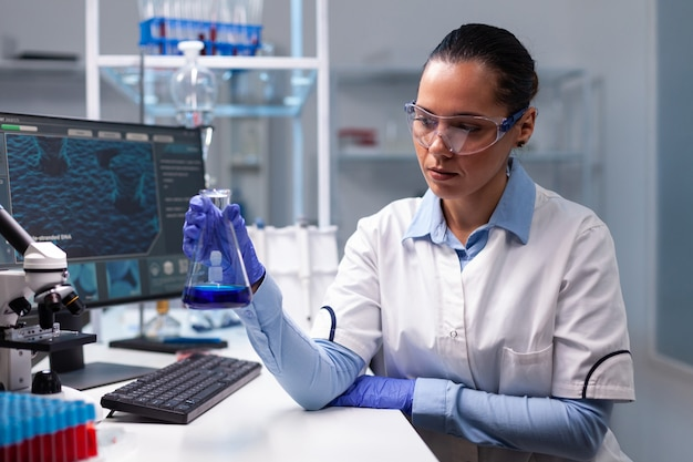Wetenschapper vrouw arts met glazen kolf analyseren van vloeibare oplossing