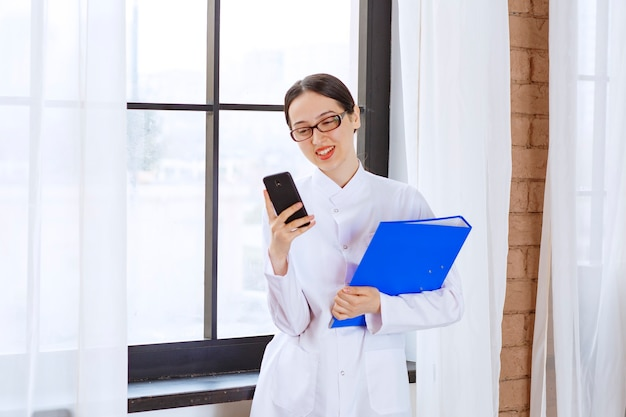 Wetenschapper vrouwelijke bedrijf map en mobiele telefoon in de buurt van venster.