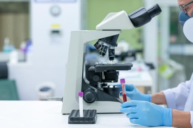Wetenschappers bestuderen onderzoek naar de ziektekiemen die covid-19 veroorzaken, de belangrijkste oorzaak van ziekte en die zich over de wereld verspreiden. (focus op buis)
