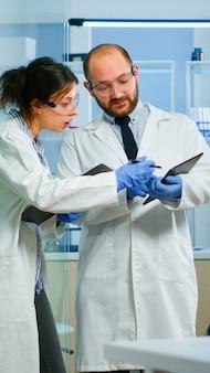 Wetenschappers-collega's die digitale tablet gebruiken die in een medisch onderzoekslaboratorium werken, biochemische monsters analyseren, praten. wetenschappelijk laboratorium voor geneeskunde, ontwikkeling van microbiologie met geavanceerde apparatuur