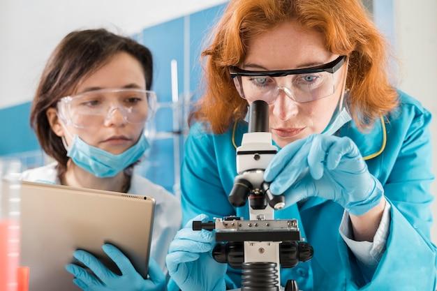 Wetenschappers die door een microscoop kijken